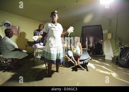 Carrefour, Haïti, infirmière avec bouteille de perfusion à la main, debout dans l'eau Banque D'Images