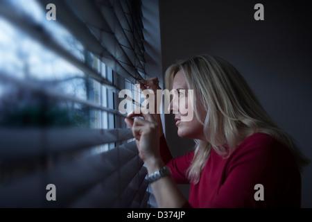 Profil d'une femme avec de longs cheveux blonds, à travers une fenêtre aveugle de l'intérieur à la lumière, est Banque D'Images