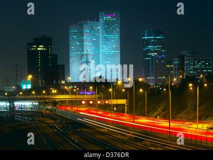 Vue de nuit sur la ville au centre-ville de Tel Aviv, Azrieli Towers et allumé la lumière des traces sur l'autoroute Banque D'Images