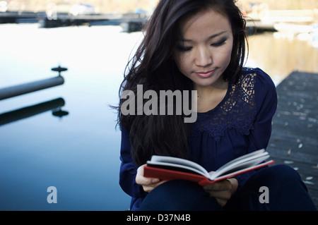 Woman reading on deck en bois Banque D'Images