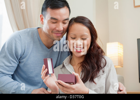 Man giving girlfriend gift on sofa Banque D'Images