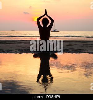 Yoga woman sitting in lotus pose sur la plage pendant le coucher du soleil, avec la réflexion dans l'eau