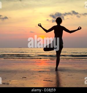 Yoga woman effectue un exercice sur la plage pendant le coucher du soleil, avec la réflexion dans l'eau