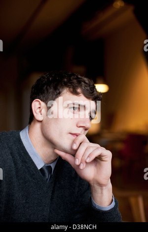Businessman thinking with chin in hand Banque D'Images