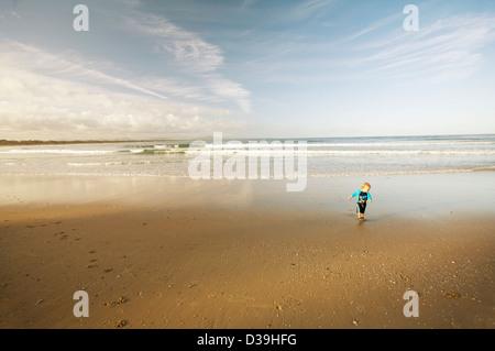Petit garçon en maillot bleu / sunsuit sur une plage Banque D'Images