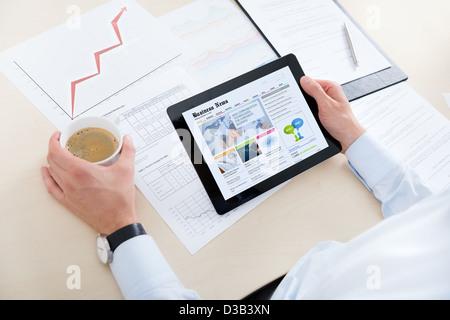 Businessman à boire du café en milieu de travail et à la recherche les dernières news sur ordinateur numérique moderne. Banque D'Images