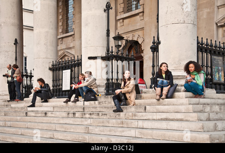 Les touristes et les habitants assis sur les marches de St Martin dans les champs à l'angle de l'église de Trafalgar Banque D'Images