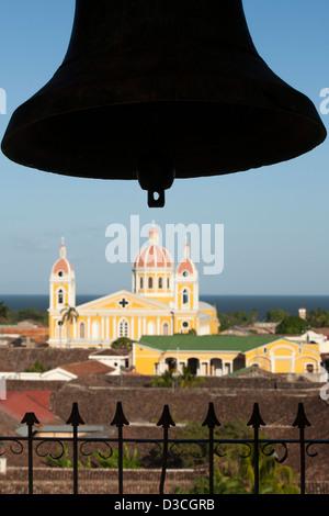 Une vue de la Cathédrale de Grenade jaune vif avec une cloche en silhouette pris de la tour de La Merced au Nicaragua Banque D'Images