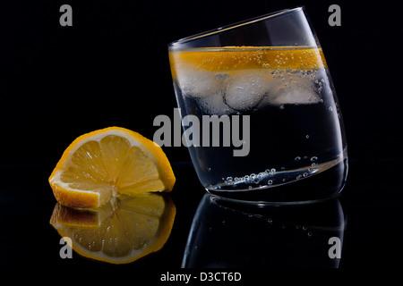 Gin Tonic ou de vodka tonic avec une tranche de citron sur fond noir Banque D'Images