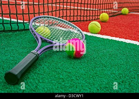 Ball et tennis racket organisé autour du filet sur un terrain synthétique. Banque D'Images