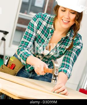 Un Feamle travaille sur un projet dans l'atelier de réparation Banque D'Images