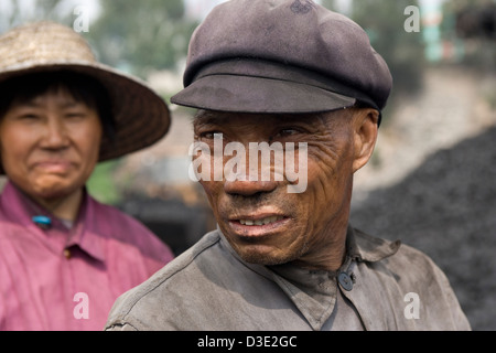 DATONG, province de Shanxi, Chine - AOÛT 2007: Li Yu, 64 ans, prend une pause à partir de charbon de tri sur un convoyeur à bande à une mine privée près de Datong. Banque D'Images