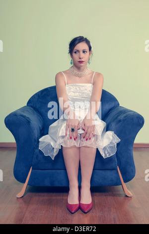 Une femme en robe blanche est assis sur un fauteuil bleu