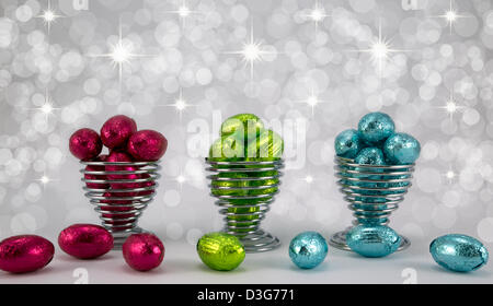 Foil wrapped Easter Eggs in eggcups fil et diffus sparkle background. Banque D'Images