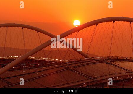 (Afp) - Le soleil se couche derrière le spectaculaire toit du Stade Olympique d'Athènes, Grèce, 4 août 2004. Les Banque D'Images