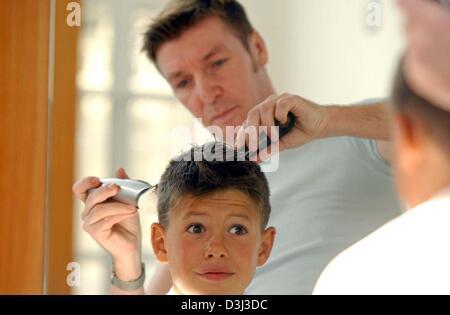 (Afp) - Un garçon tire un visage alors qu'il a couper les cheveux à un coiffeur à Munich, Allemagne, 12 Novembre Banque D'Images