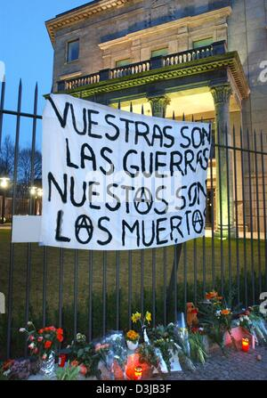 """(Afp) - Une bannière est suspendu au-dessus des bouquets de fleurs et de bougies attaché à une clôture entourant l'ambassade d'Espagne à Berlin, 14 mars 2004. La bannière indique 'Vuestras las Guerras, nuestros fils fils los muertos"""" (votre guerre et nos morts). Environ 30 personnes se sont réunies pour un rassemblement pour protester contre la politique du gouvernement espagnol. 200 personnes sont mortes et plus de 1 200 ont été blessés dans un"""