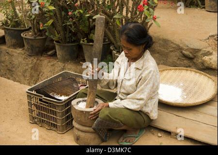 Une femme est assise sur les étapes de la préparation de farine de riz à l'aide d'un grand mortier et pilon Banque D'Images