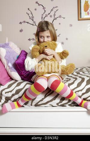 9 ans, fille, assise sur son lit serrant un ours en peluche Banque D'Images