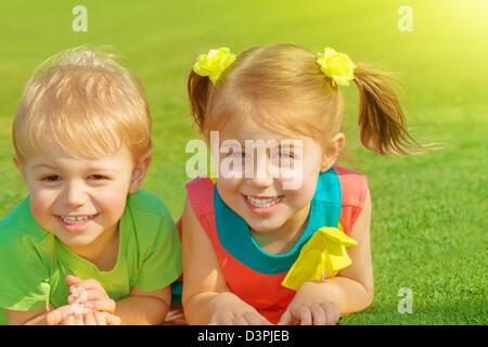 Photo de petit frère et sœur couchée sur l'herbe verte champ dans journée ensoleillée, deux adorables enfant jouant Banque D'Images