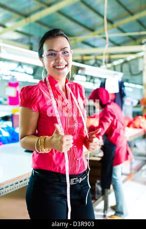 Asiatique femme couturière ou concepteur fièrement dans une usine textile, c'est son lieu de travail Banque D'Images