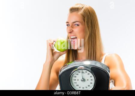 Le régime alimentaire et le poids, jeune femme avec l'échelle sous le bras et Apple Banque D'Images