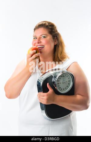 Le régime alimentaire et le poids, obésité jeune femme avec l'échelle sous le bras et Apple Banque D'Images