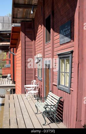 Banc, chaises et une petite table sur la terrasse à l'eau en face d'une traditionnelle maison en bois rouge à Porvoo, Banque D'Images