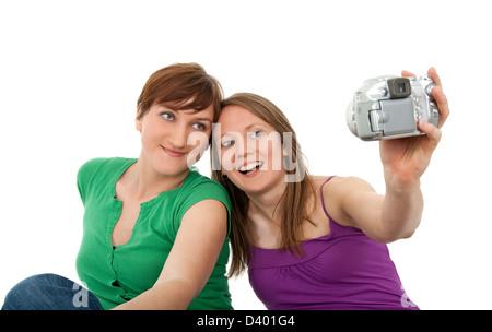 Deux jeunes femmes prenant un auto-portrait avec un appareil photo numérique. Banque D'Images