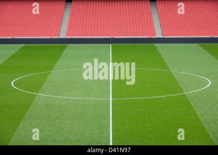 Cercle de centre d'un terrain de football et un coin rouge vif à l'intérieur d'un stade de football vide.