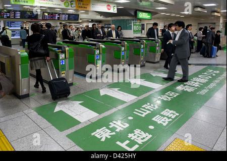 Les hommes d'affaires et les voyageurs de passage aux guichets électroniques sur leur façon de plates-formes de Banque D'Images
