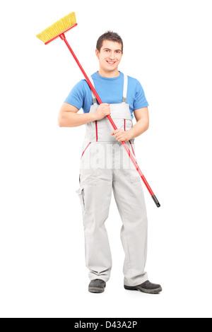 Full Length portrait of a smiling cleaner dans un uniforme avec un balai contre isolé sur fond blanc Banque D'Images