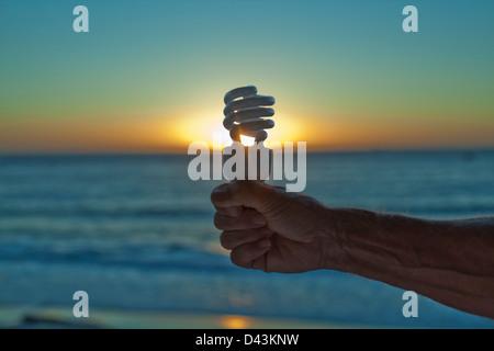 Main tenant Lightbulb au coucher du soleil, Cape Town, Western Cape, Province du Cap, Afrique du Sud Banque D'Images