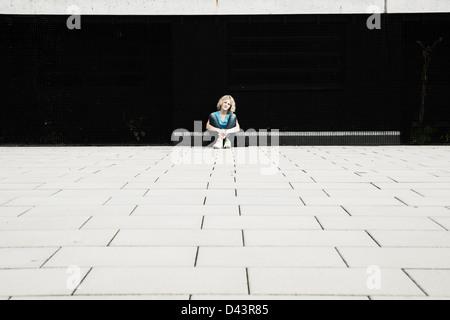 Fille assise sur le terrain en aire de jeux, Mannheim, Baden-Wurttemberg, Germany Banque D'Images