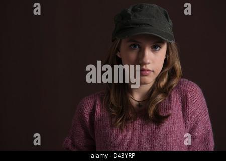 Close-up Portrait of Teenage Girl, blonde wearing Baseball Hat, Studio Shot sur fond noir Banque D'Images