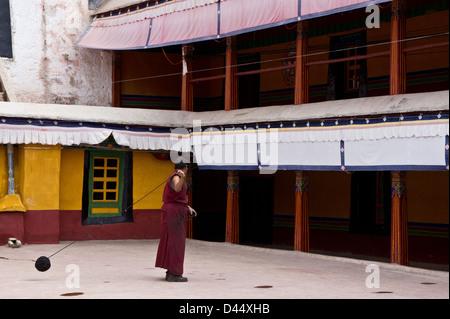 Le moine bouddhiste filage de la laine dans la cour de Drepung, à Lhassa, Tibet Banque D'Images