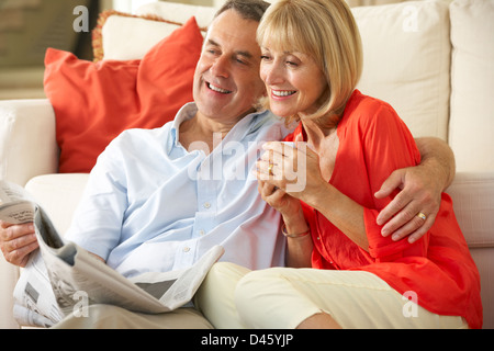 Senior Couple Relaxing On Sofa At Home Reading Newspaper Banque D'Images
