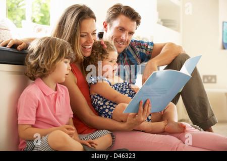 Les parents avec des enfants assis à l'intérieur Histoire de lecture Banque D'Images