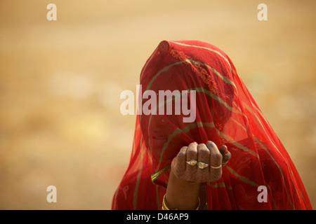 Une jeune femme indienne à la périphérie de Bikaner Rajasthan en Inde du nord. shields son visage du vent du désert Banque D'Images