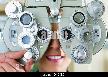 Jeune femme à phoropter à opticien ou ophtalmologue pour essai d'oeil, il est myope ou à long terme Banque D'Images
