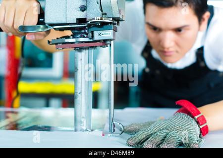 À l'aide d'un travailleur cutter - une grande machine pour couper les tissus en question- dans une usine de textiles Banque D'Images