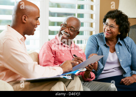 Financial Advisor Talking to Senior Couple At Home Banque D'Images