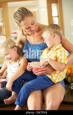 Mère et enfants de prendre le petit déjeuner assis sur le comptoir de la cuisine Banque D'Images