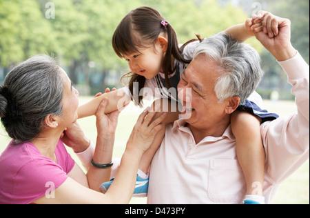 Les grands-parents chinois donnant sur petite-fille épaules Banque D'Images