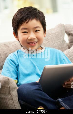 Jeune garçon chinois Using Tablet Computer assis sur le canapé à la maison Banque D'Images