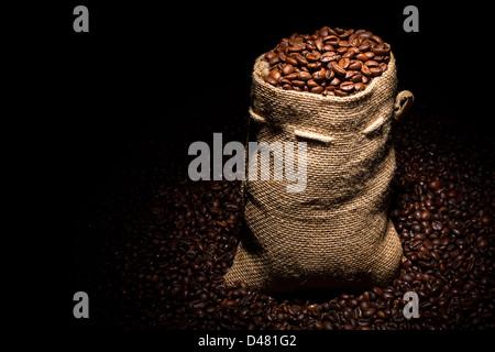 Sachet rempli de grains de café dans Spotlight Banque D'Images