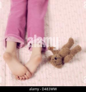 Pieds féminins en rose pyjama avec un ours en peluche Banque D'Images