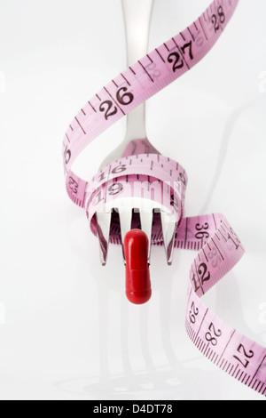 Fourche, comprimé et ruban à mesurer sur fond blanc Banque D'Images
