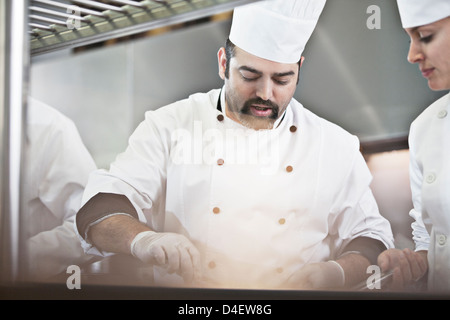 Chefs cooking in restaurant kitchen Banque D'Images