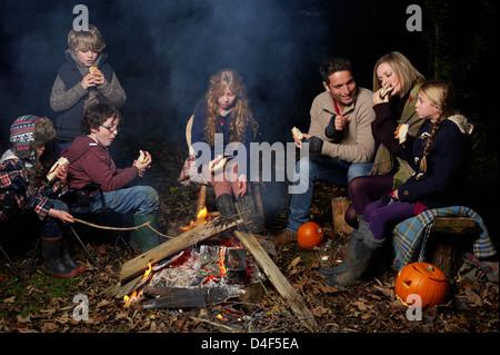 Manger en famille autour de feu de camp la nuit Banque D'Images